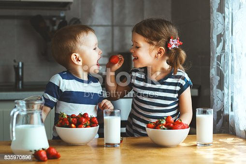 istock Happy children brother and sister eating strawberries with milk 835970896