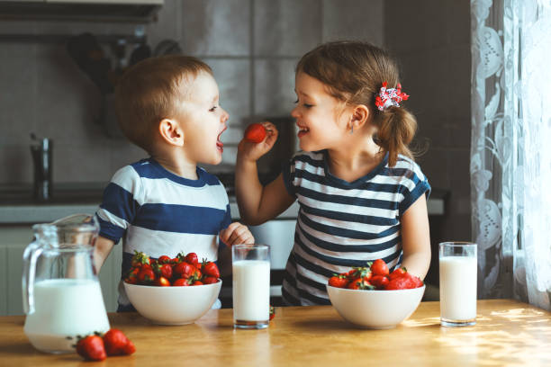 Happy children brother and sister eating strawberries with milk stock photo
