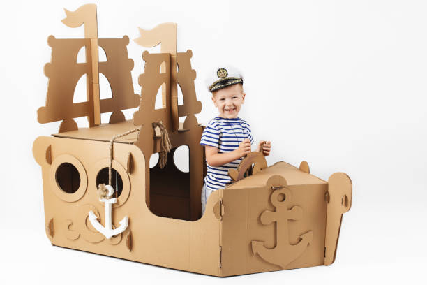 Happy children. Childhood. Fantasy, imagination. Little boy playing with cardboard ship on white background. Happy kids. Cute child dressed as a sailor. Childhood. Fantasy, imagination. sailing dinghy stock pictures, royalty-free photos & images