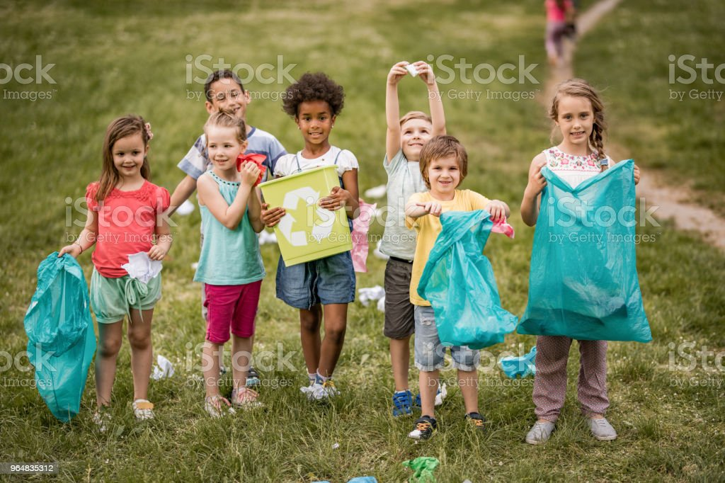 Happy children doing environmental cleanup in the park. royalty-free stock photo
