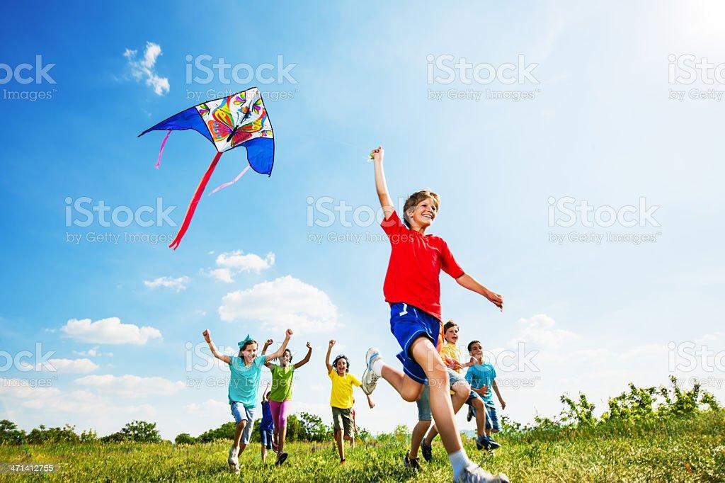 Happy children flying a kite. stock photo