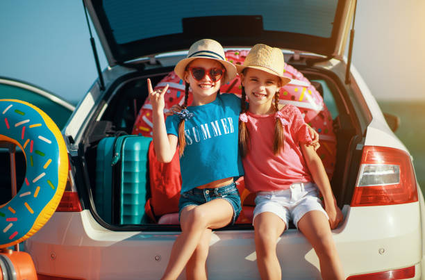 happy children girls twin sisters on the car ride to summer trip - road trip стоковые фото и изображения