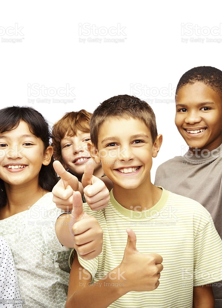 Happy children giving thumbs up in front of a white wall royalty-free stock photo