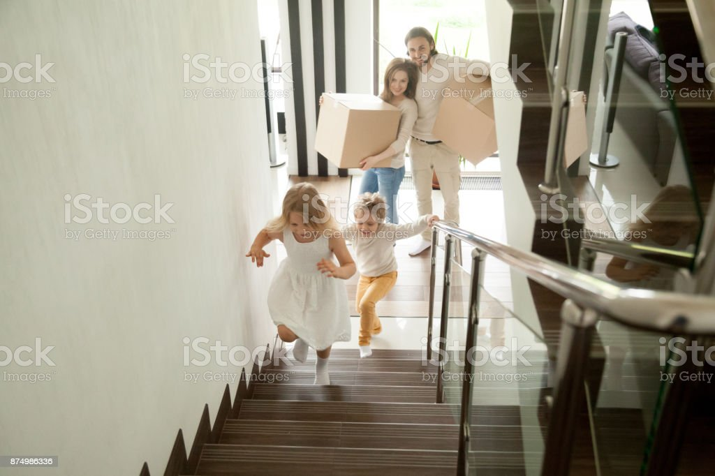 Happy children going upstairs, family with boxes moving in house Happy children going upstairs inside two story big house, excited kids having fun stepping walking up stairs running to their rooms while parents holding boxes, family moving in relocating new home 6-7 Years Stock Photo