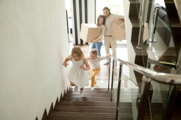 Happy children going upstairs, family with boxes moving in house stock photo