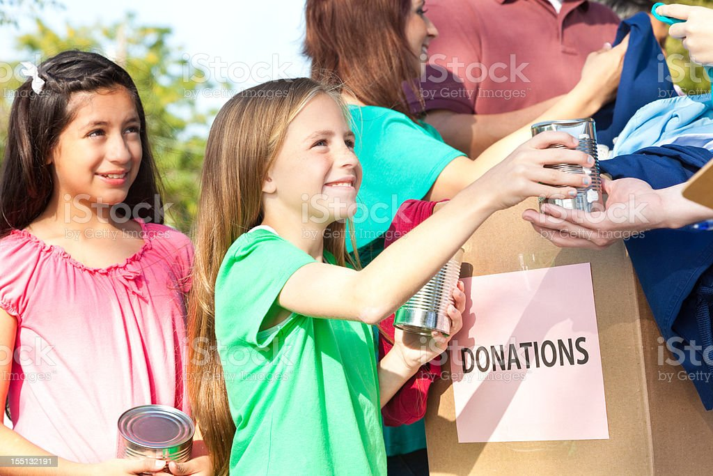 Happy children handing donations in at a donation center stock photo