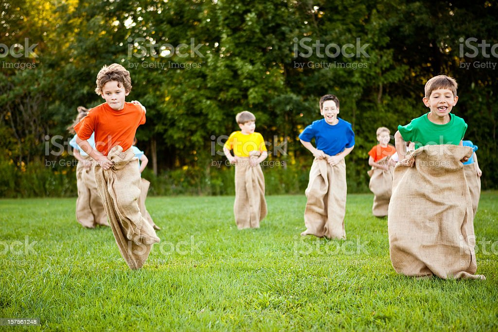 Happy Children Having a Fun Potato Sack Race Outside royalty-free stock photo