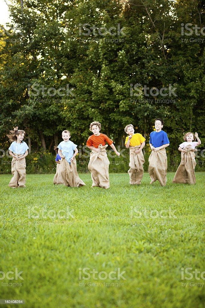 Happy Children Having a Fun Potato Sack Race Outside royalty-free stock photo