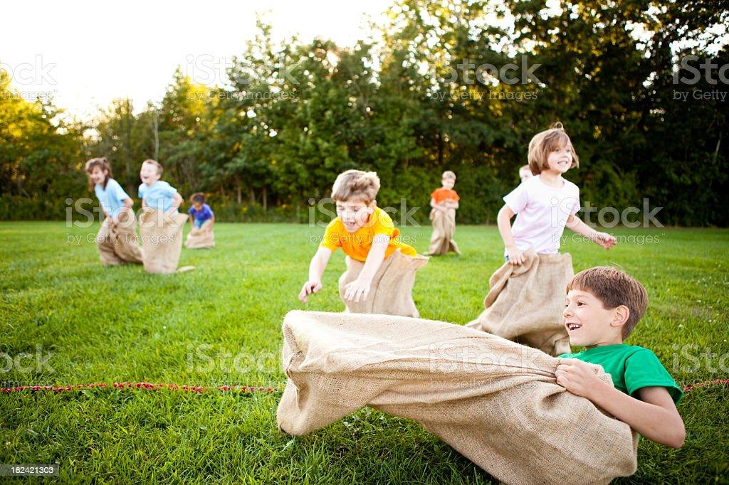 Happy Children Having a Fun Potato Sack Race Outside stock photo