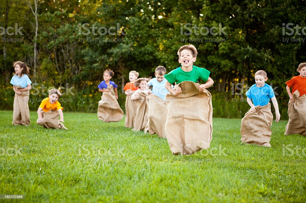 Happy Children Having a Fun Potato Sack Race Outside Color photo of a group of happy kids laughing and enjoying a potato sack race outside. 10-11 Years Stock Photo