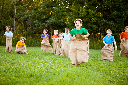 Happy Children Having A Fun Potato Sack Race Outside Stock Photo - Download Image Now