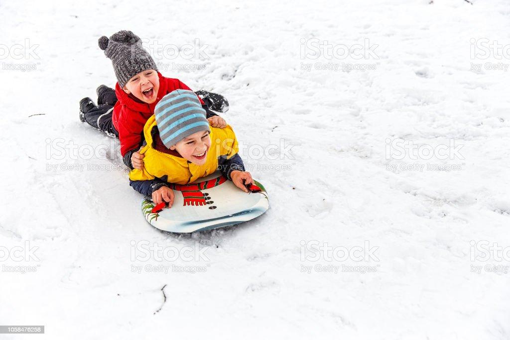 happy children having fun sliding down the hill stock photo
