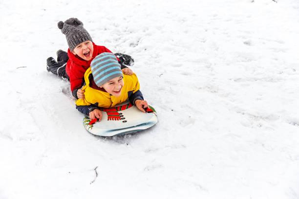 glückliche kinder spaß bergab schieben - schneespiele stock-fotos und bilder