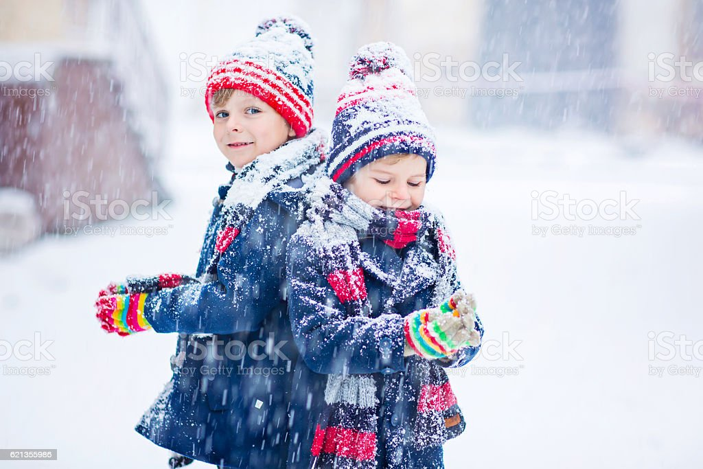 Happy children having fun with snow in winter stock photo
