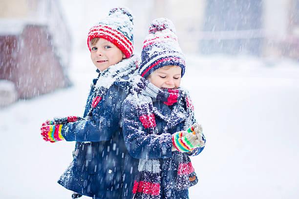 glückliche kinder spaß haben mit schnee im winter - schneespiele stock-fotos und bilder