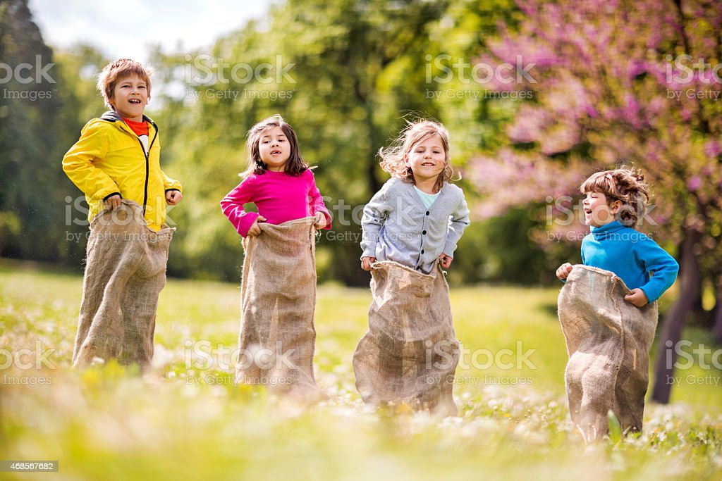Happy children having sack race in the park. stock photo