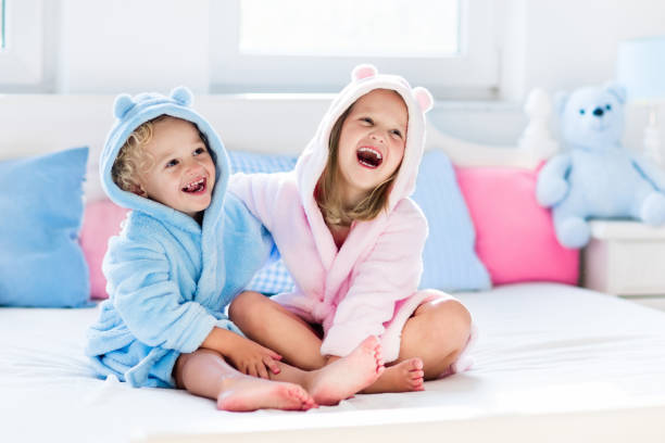 happy children in bathrobe or towel after bath - badewannenkissen stock-fotos und bilder