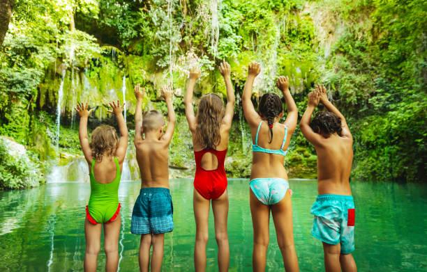 Glückliche Kinder springen in den Bergsee – Foto