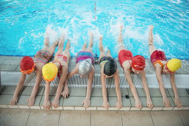 feliz grupo de niños en la clase de piscina, aprender a nadar - foto de stock
