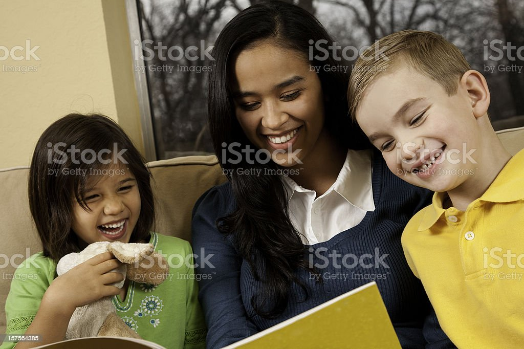 Happy Children Laughing While Reading Book With Baby Sitter royalty-free stock photo