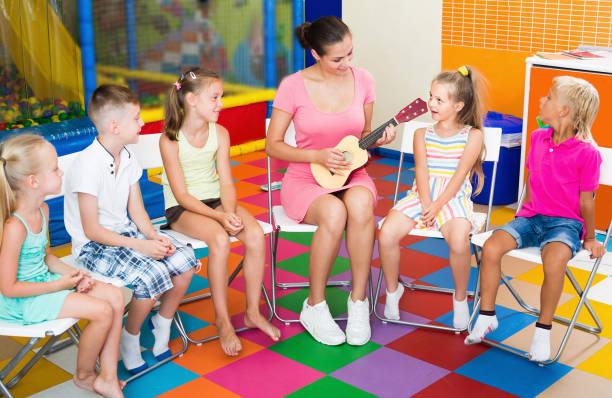 glückliche kinder zuhören kleinen gitarre lehrer - ukulele songs stock-fotos und bilder