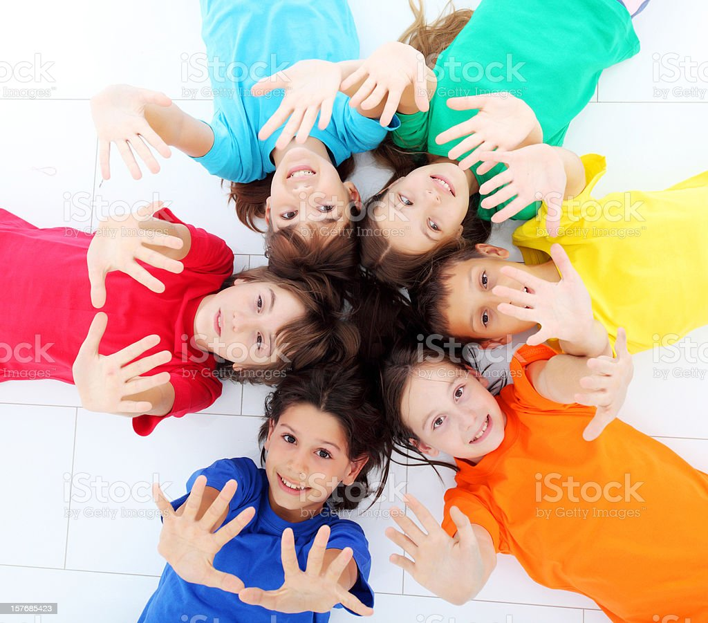 Happy children lying down in circle with palm up royalty-free stock photo