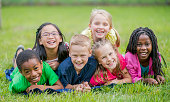 A happy, diverse group of primary school age children lie together in the grass in the park.