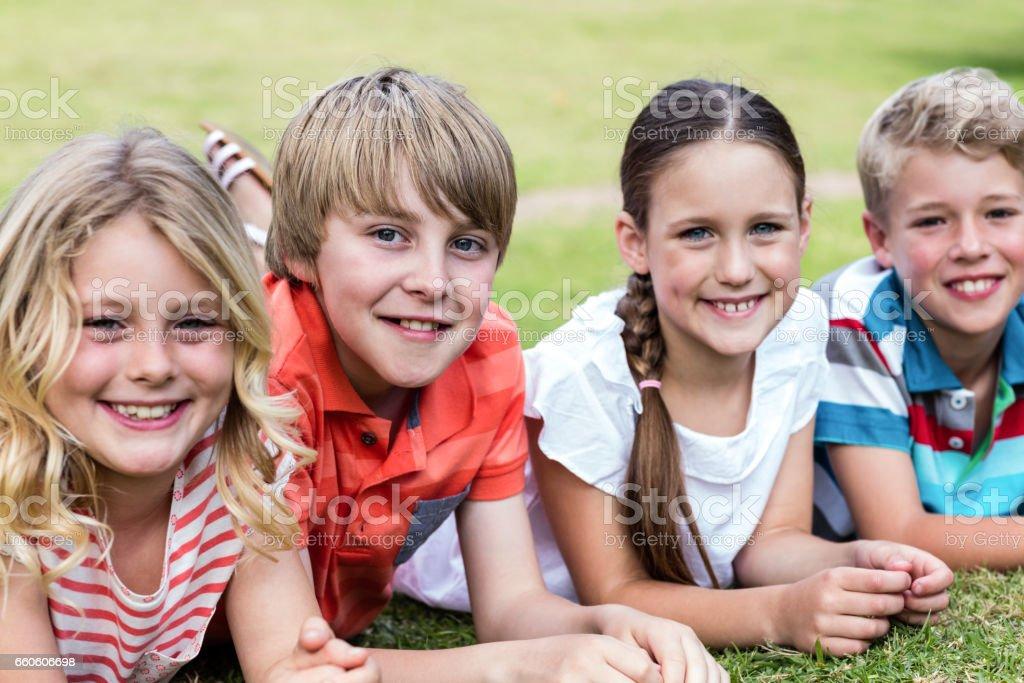 Happy children lying on grass royalty-free stock photo