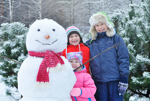 Happy children make a snowman in the winter
