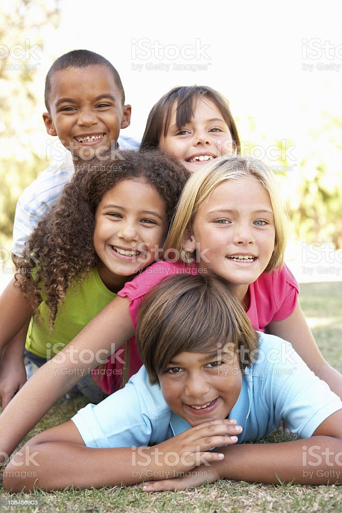 5 happy children of different races piled up in park Group Of Children Piled Up In Park smiling at camera  6-7 Years Stock Photo