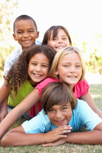 5 Happy Children Of Different Races Piled Up In Park Stock Photo - Download Image Now