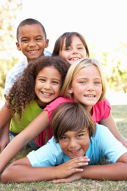 5 happy children of different races piled up in park - vertical stock pictures, royalty-free photos & images