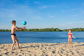 Happy children on the beach play with a ball. Summer holidays. Lifestyle.