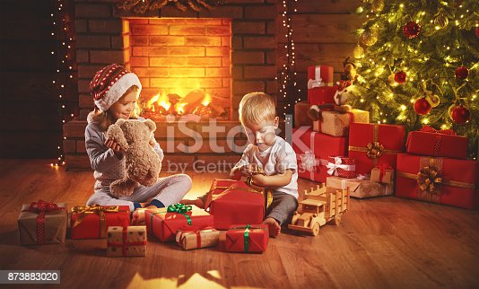 868220646istockphoto happy children open Christmas gifts at night at Christmas tree 873883020