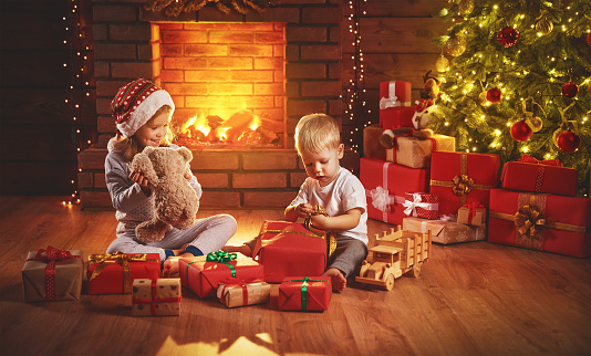 868220646 istock photo happy children open Christmas gifts at night at Christmas tree 873883020