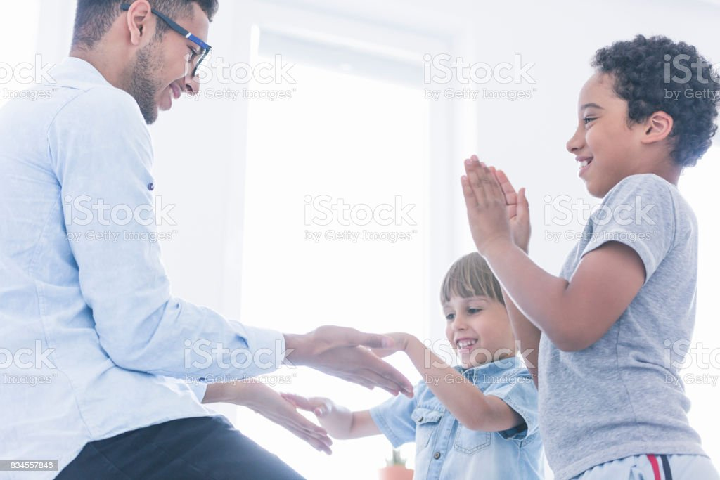 Happy children play clapping hands stock photo