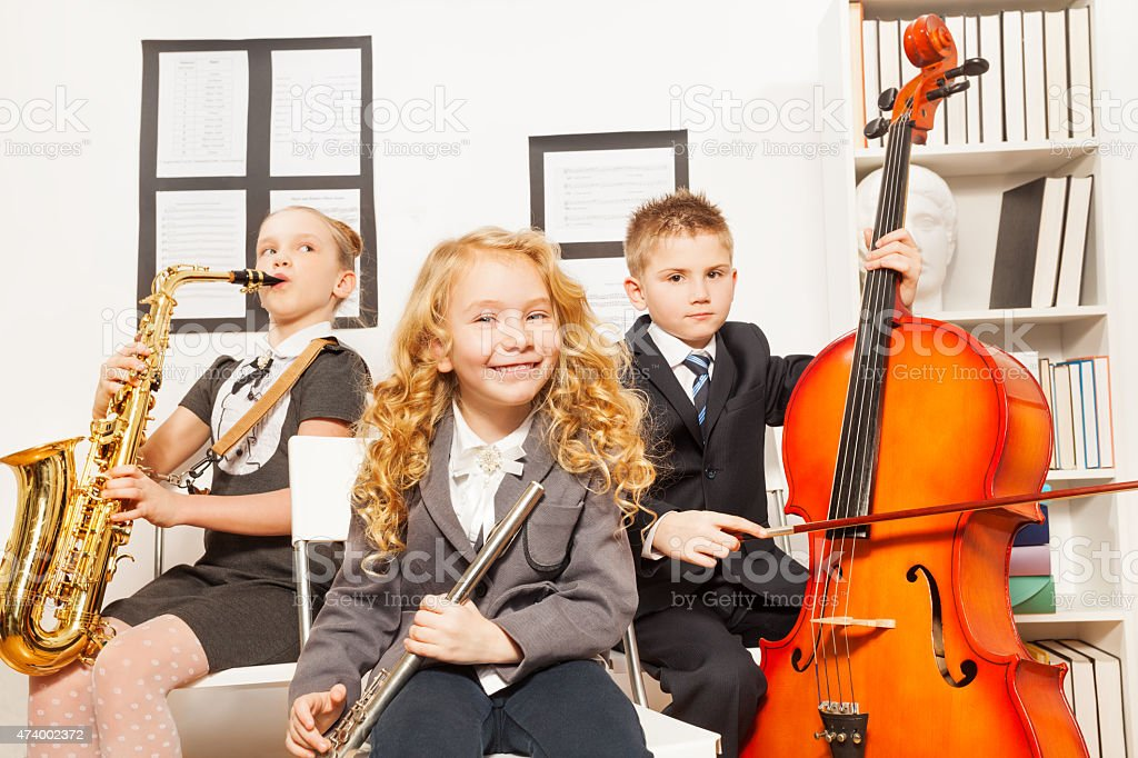 Happy children play musical instruments together stock photo