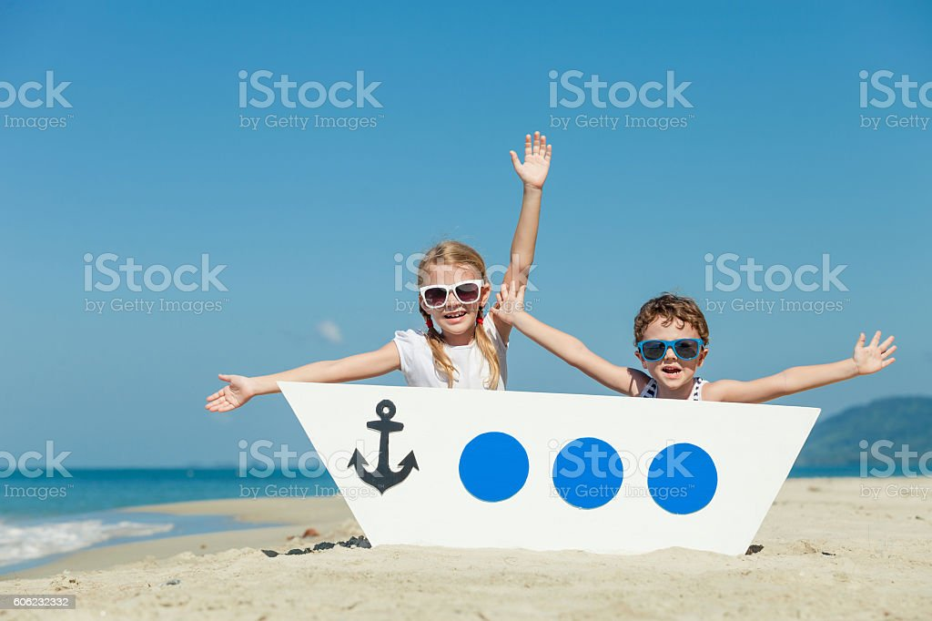 Happy children playing on the beach at the day time. stock photo