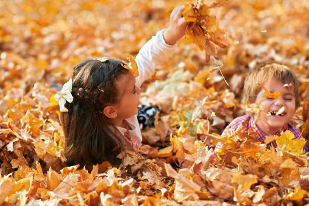 Niños felices jugando, posando, sonriendo y divirtiéndose en el parque de la ciudad de otoño. Arboles y hojas de color amarillo brillante - foto de stock