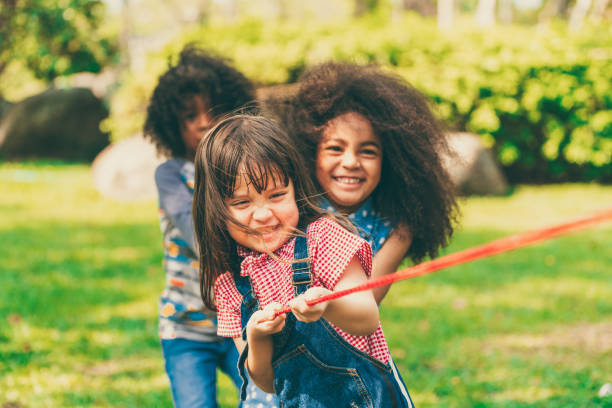 Happy children playing tug of war and having fun during summer camping in the park. Happy children playing tug of war and having fun during summer camping in the park. Children recreation concept. recreational pursuit stock pictures, royalty-free photos & images