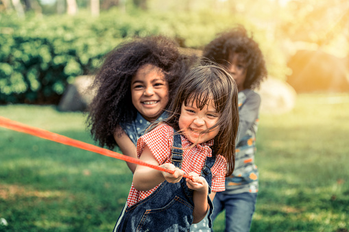 istock Happy children playing tug of war and having fun during summer camping in the park. Children recreation concept. 1128161171