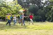 Happy children playing with a kite in the park