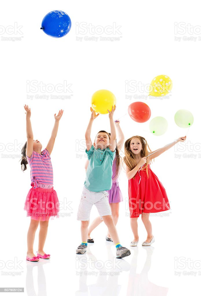 Happy children playing with balloons together. stock photo