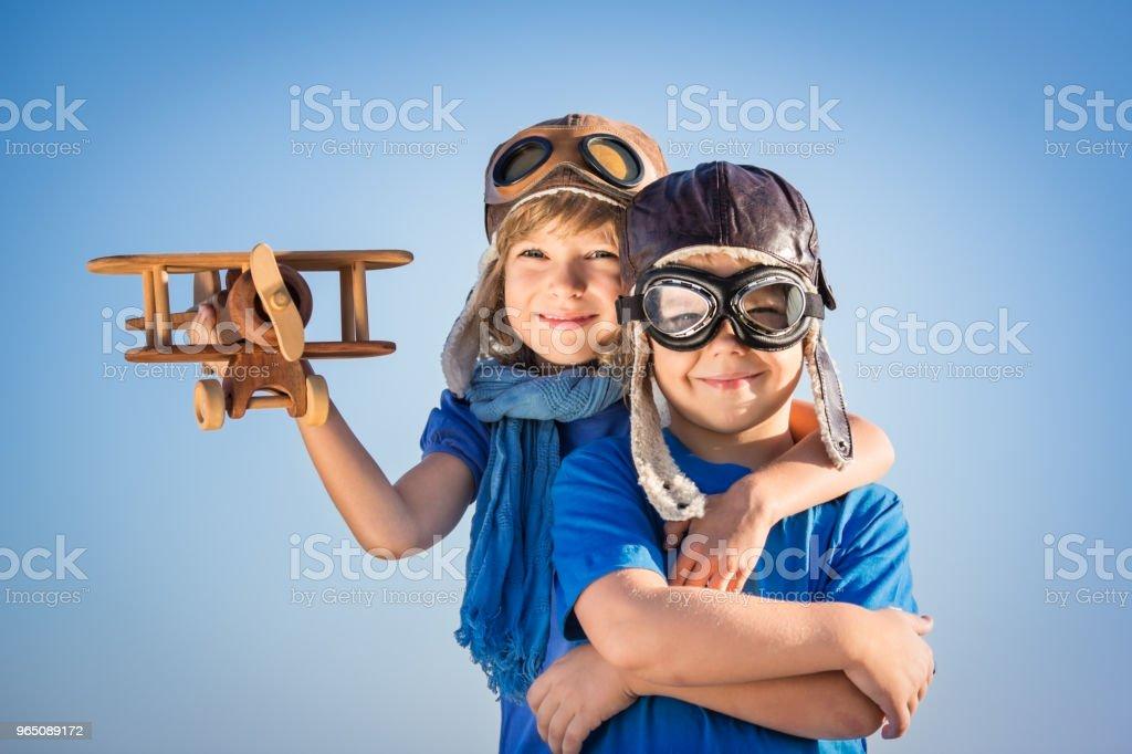 Happy children playing with toy airplane zbiór zdjęć royalty-free