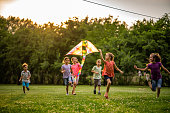 Happy children flying a kite in the park.