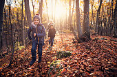 Three kids running in autumn forest. Kids are aged 8 and 11.\nNikon D850