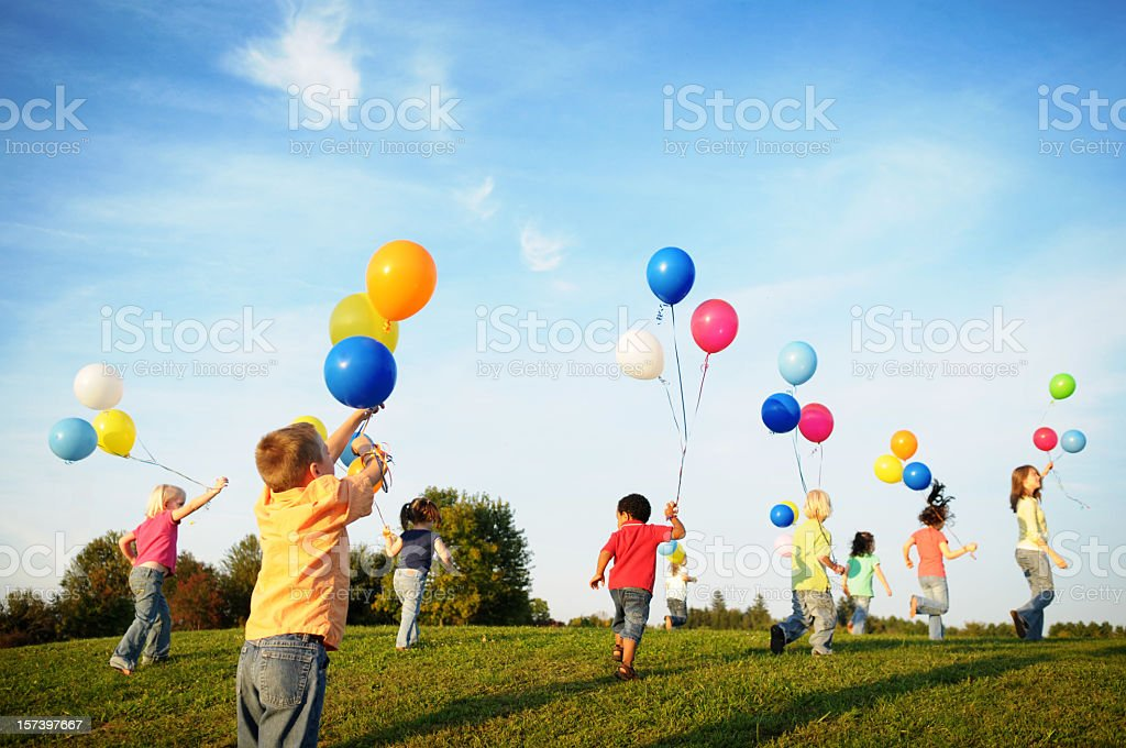 Happy children running in field with balloons stock photo
