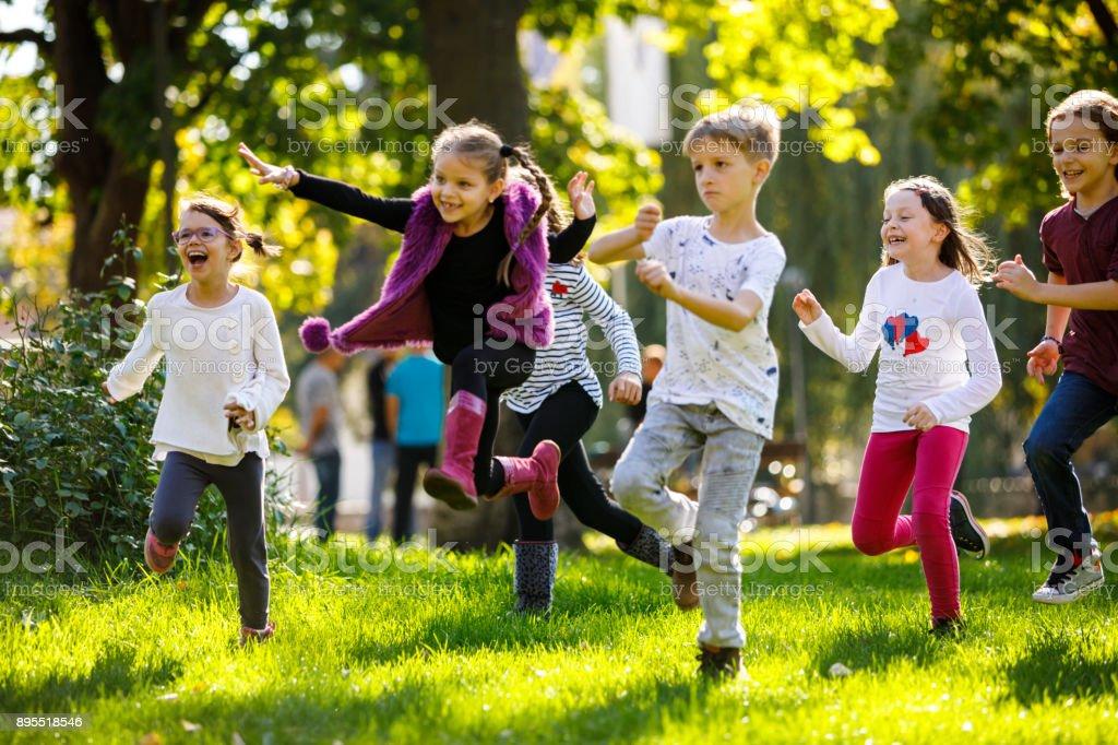 Happy children running outside stock photo
