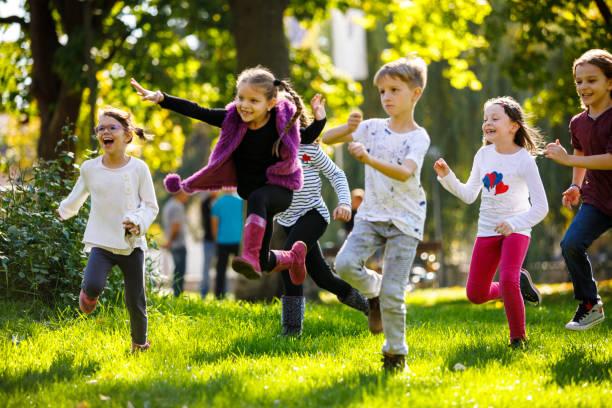 glückliche kinder laufen außerhalb - grundschule stock-fotos und bilder