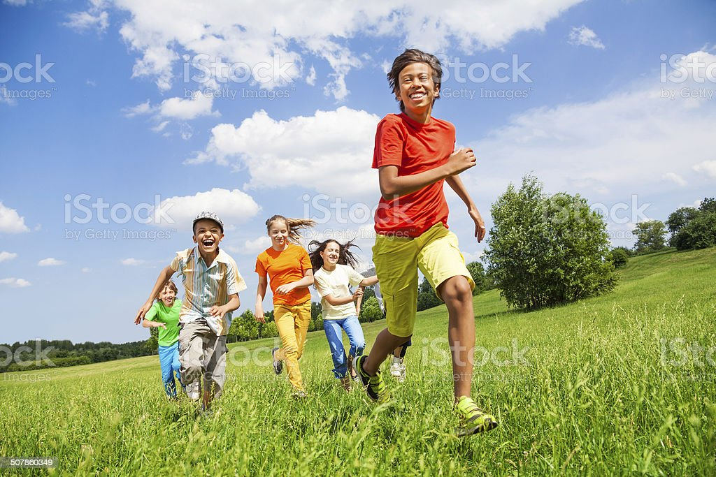 Happy children running together in the field stock photo